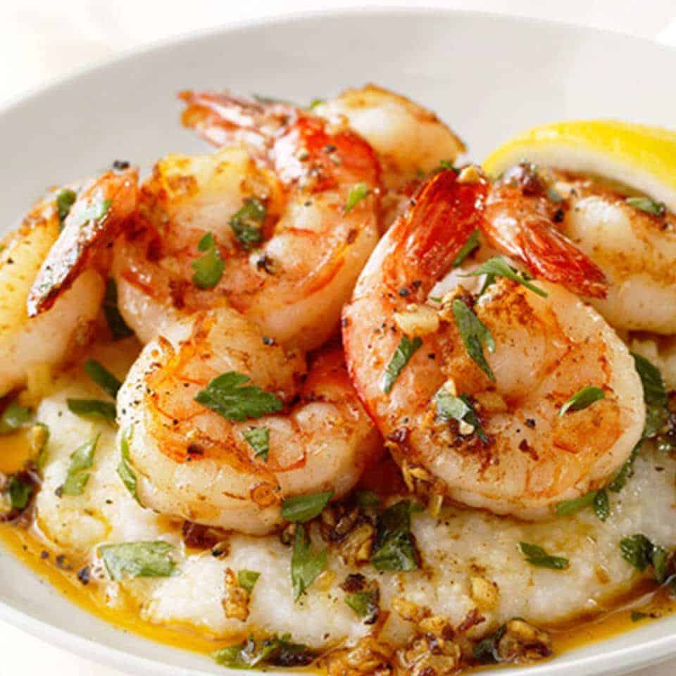 succulent grilled shrimp piled high atop a fluff bed of buttery southern grits garnished to perfection