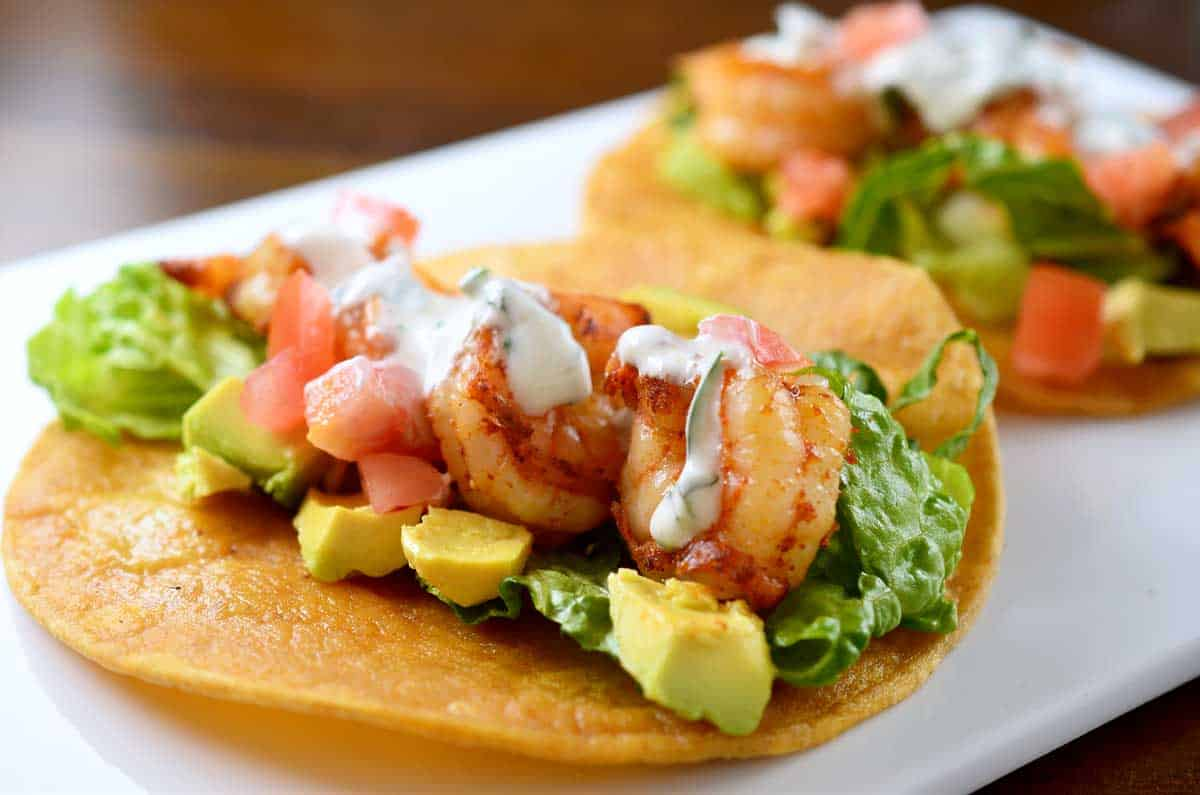 tasty shrimp tacos in a corn tortilla with avacado, lettuce, tomato and ranch