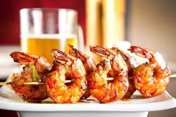 bbq glazed shrimp on skewers with a cold beer.